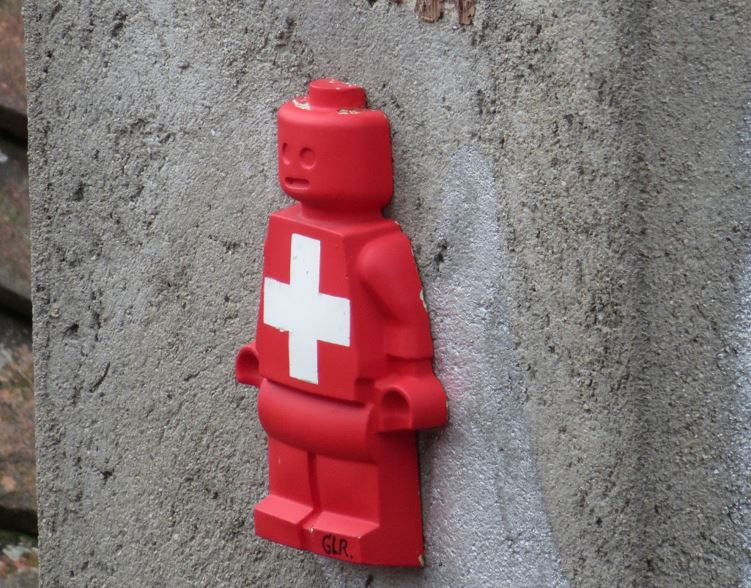 Lego character with Swiss flag on wall - Credit: chaoticjourney.com